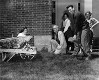 "Students with wheelbarrow and shovel and President Johnson at ""1941"" cornerstone (Johnson Day?)"