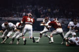 Alabama linebacker Randy Scott (#50) tackling an Arkansas player during the 1980 Sugar Bowl game at the Superdome in New Orleans, Louisiana.