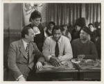 """Eslanda Goode Robeson (standing), Paul Robeson (center), and Lawrence Brown (right) in a scene from the motion picture """"Big Fella"""""""