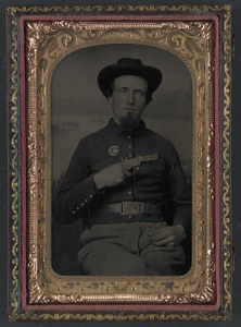 [Unidentified soldier in Union shell jacket with 7th Corps Dept. of Arkansas insignia and 1851 rectangular eagle belt plate holding volcanic pistol to his chest]