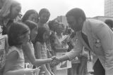 """Andrew Young shaking hands with a little girl in a crowd in downtown Atlanta, Georgia, during the Democratic National Committee's regional conference, """"Victory '68."""""""