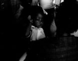 Woman holding a small girl inside Mt. Moriah Baptist Church in Hayneville, Alabama, during the first anniversary celebration of the Lowndes County Christian Movement.