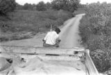 Man driving a tractor down a dirt road near Mount Meigs in Montgomery County, Alabama.