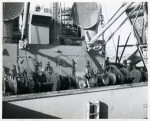 Corporal Calvin James of Alabama, and Technician Fifth Grade Joseph Wooten of North Carolina, operating a winch aboard a Liberty ship in the harbor at Marseille