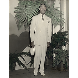 Fashion model Louie Smith in white suit standing and holding hat
