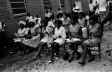 Audience seated in chairs outside a brick church building in Prattville, Alabama, during a civil rights meeting of the Autauga County Improvement Association.