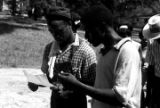 Edward Rudolph and another man, reading a sheet of paper while leading marchers down a street in Prattville, Alabama, during a demonstration sponsored by the Autauga County Improvement Association.