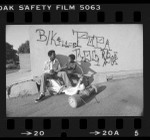 Herman Akins and Steven White sitting under graffiti that helped in investigation of killings in West Los Angeles, Calif., 1980