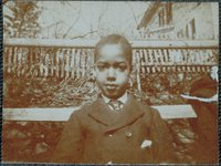 Thumbnail for African-American boy in front of a picket fence