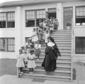Nun lining up children on the steps in front of Nazareth Catholic Mission in Montgomery, Alabama.