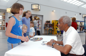 Retired astronaut Dr. Guion S. Bluford, the first African-American to fly in space, greets and signs autographs for Kaleigh, Juleigh, Ashleigh, and Emaleigh Morford at Royal Air Force (RAF) Mildenhall, United Kingdom (UK). Dr. Bluford is visiting numerous bases throughout Europe as part of the Extreme Summer Tour activities organized by Air Force Services