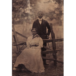 African-American couple posing by a fence