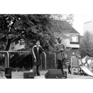 Two young men perform on an outdoor stage in Villa Victoria neighborhood.