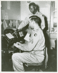Corporal Parkins D. Peck, chief teletype operator, seated at the teletype machine while African American Private James Lee stands behind him and points to a Western Union telegram form, Camp Edwards, Kentucky