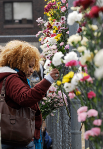 Justice for Jason rally at UMass Amherst: UMass graduate student Iris Jacob, places a flower on a fence near the dormitory of Jason Vassell