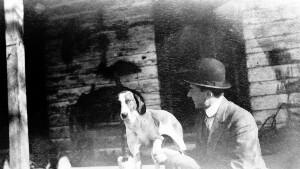 Unidentifed man shaking dogs leg.