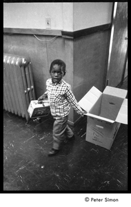 Young boy with a cardboard box and Peanuts lunch pail, Liberation School