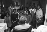 """Children in the group """"Buds of Promise"""" from Mt. Zion AME Zion Church in Montgomery, Alabama, singing to Ethel Reynolds in her home."""