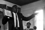 Willie Lee Wood, Sr., demonstrating a voting machine for an audience in a small wooden church building in Prattville, Alabama.