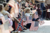 Spectators waving American flags at the Veterans Day parade in Birmingham, Alabama.