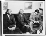 [Two unidentified African American men seated on a sofa, talking to a young man, possibly a reporter]