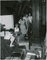 Maid, two workmen, and two other staff members packing books