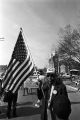 Man carrying an American flag during the 20th anniversary reenactment of the Selma to Montgomery March in Selma, Alabama.