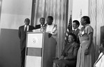 Black Family Reunion press conference participants listening to Bill Cosby, Los Angeles, 1987