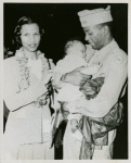 African American officer standing next to his wife and holding his baby son in his hands, Honolulu