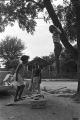 Diane Foster and Elizabeth Ellis playing on a make-shift seesaw in the dirt yard in front of a brick house in Newtown, a neighborhood in Montgomery, Alabama.