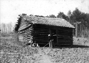 African-American man & woman in front of log house