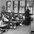 Priest calling on students with their hands raised in a classroom at Nazareth Catholic Mission in Montgomery, Alabama.