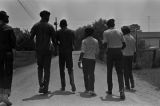 Young men and women walking down a dirt road in a neighborhood in Montgomery, Alabama, while canvassing voters in the city.