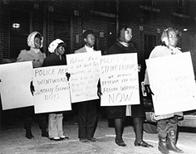 African American workers picket with placards announcing their strike against the Wentworth Manufacturing Company and decrying police behavior and arrests of co-workers, 1968