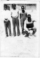Three Boys Stand Next to a Baseball Catcher, circa 1942