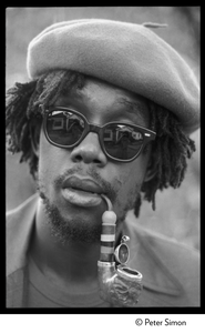 Peter Tosh: portrait wearing beret, dark glasses, and smoking a pipe