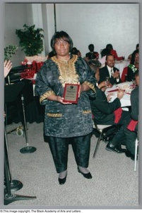 Woman receiving plaque at Christmas Kwanzaa soiree Christmas/Kwanzaa Soiree
