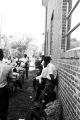 Stokely Carmichael addressing a group of people standing outside a brick church building in Prattville, Alabama, during a meeting of the Autauga County Improvement Association.
