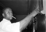 Charlie Marshall, a cook at the Laicos Club in Montgomery, Alabama, using a pay phone.
