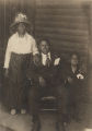 African American man seated on a porch with his wife and young son.