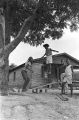 Elizabeth Ellis and Diane Foster playing on a make-shift seesaw in the dirt yard in front of a brick house in Newtown, a neighborhood in Montgomery, Alabama.