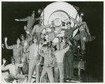African American soldiers standing on the front of a stationary train and waving to the camera