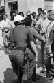 Police officer patting down a demonstrator during a Black Panther march down 20th Street South in downtown Birmingham, Alabama.