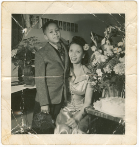 Photograph of Mae Reeves and a young boy at her hat shop