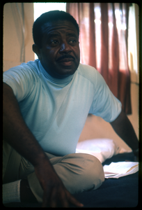 Rev. Ralph Abernathy seated on a hotel room bed