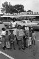 Woman and children standing in United Durham Incorporated Supermarket parking lot.