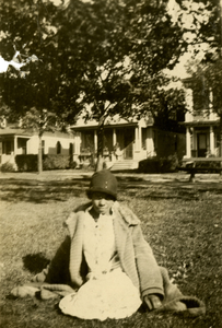 Francis Sullivan sitting on lawn with houses in background