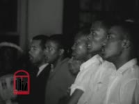 WSB-TV newsfilm clip of a mass meeting held at First Baptist Church where Dr. Martin Luther King, Jr. encourages nonviolence during a riot outside, Montgomery, Alabama, 1961 May 21