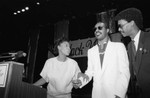 Maxine Waters, Stevie Wonder, and Ron Glass stand at a lectern during a Black Women's Forum event, Los Angeles, 1984