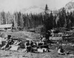 Men sitting on large rocks eating and cooking lunch. In the background can be seen stacks of lumber, a mill and a wagon.